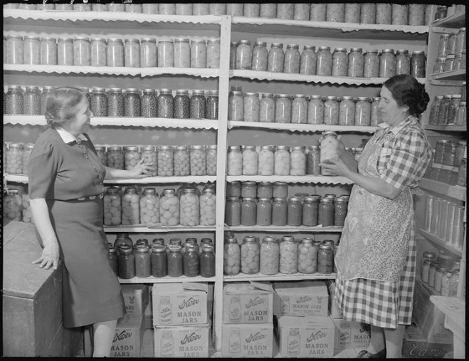New Mexico. Mrs. Fidel Romero proudly exhibits her canned food.. [Two women standing in a kitchen pantry. Pantry contains preserved fruits and vegatables.]